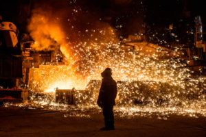 Steelworker near a blast furnace with sparks. Foundry. Heavy industry.